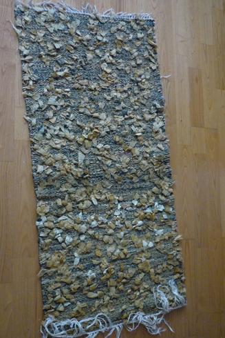 tapis tissé sur chaîne lin et or avec le journal Le Monde, enduit à l'huile et decoupé en bandes torsadées